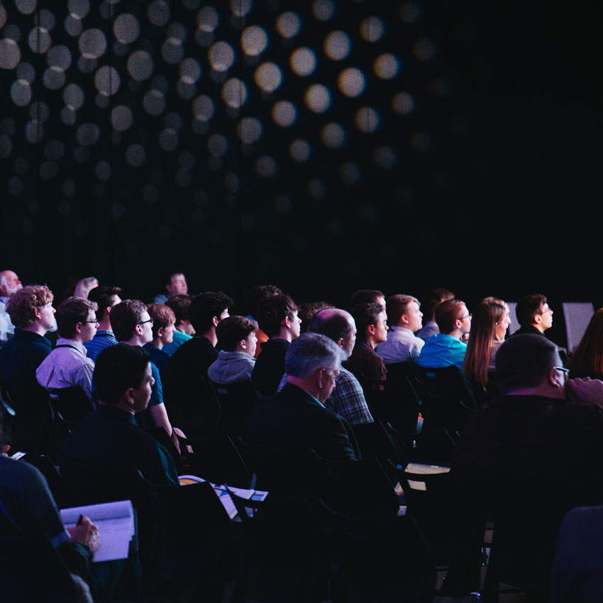 Large full width photo of people sitting in a conference centre looking right towards the front where the speaker is